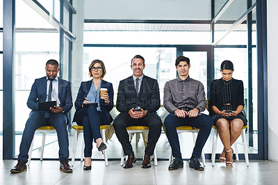 Buy stock photo Full length shot of two businesspeople waiting in line for an interview in a modern office