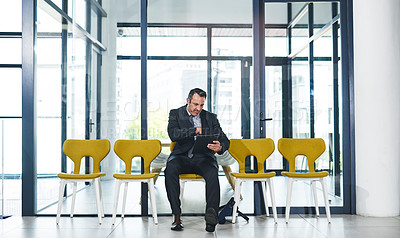 Buy stock photo Full length shot of a handsome mature businessman looking at a file while waiting in line for an interview in a modern office