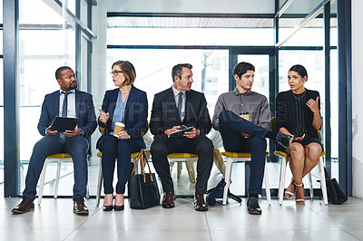 Buy stock photo Full length shot of a diverse group of businesspeople conversing with each other while sitting in line for an interview in a modern office