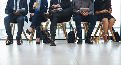 Buy stock photo Cropped shot of a group of unrecognizable businesspeople sitting in line for an interview in a modern office