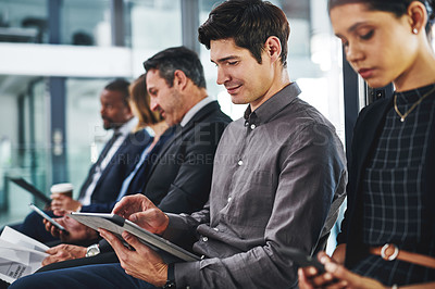 Buy stock photo Cropped shot of a diverse group of businesspeople sitting in line for an interview in a modern office