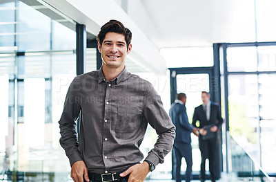Buy stock photo Cropped portrait of a handsome young businessman smiling in a modern office with his colleagues in the background