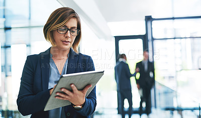Buy stock photo Cropped shot of an attractive young businesswoman using a digital tablet in an office with her colleagues in the background