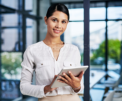 Buy stock photo Cropped portrait of an attractive young businesswoman smiling while using a digital tablet while standing in a modern office