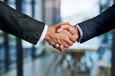 Buy stock photo Cropped shot of two unrecognizable businesspeople shaking hands in a modern office