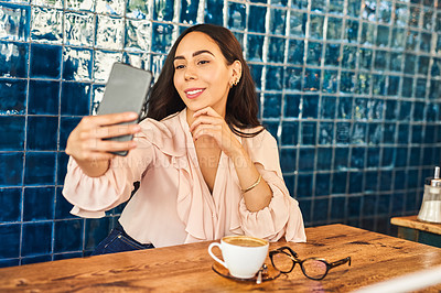 Buy stock photo Cropped shot of a beautiful woman taking a selfie while sitting in a cafe