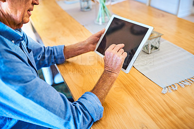 Buy stock photo Cropped shot of an unrecognizable senior man using a digital tablet while relaxing alone at home