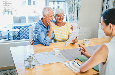 Buy stock photo Shot of a happy senior couple consulting with their financial advisor at home