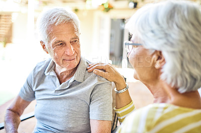 Buy stock photo Shot of a senior couple relaxing together in the backyard at home