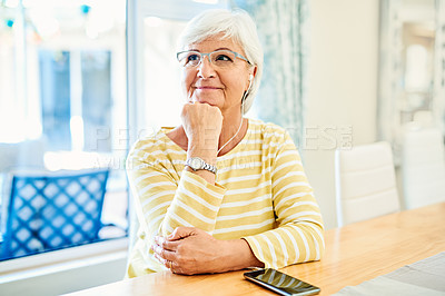 Buy stock photo Shot of a senior woman listening to music with a smartphone at home