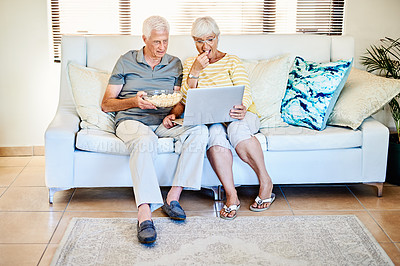 Buy stock photo Shot of a senior couple watching movies on their laptop on the sofa at home