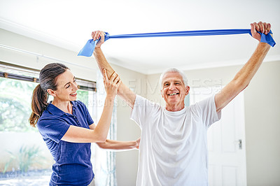 Buy stock photo Shot of a physiotherapist assisting a senior man with a resistance band