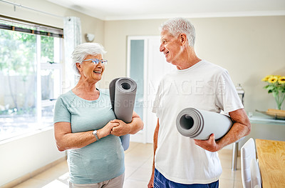 Buy stock photo Shot of a senior couple holding exercise mats while standing indoors