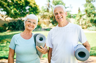 Buy stock photo Portrait of a senior couple holding exercise mats while standing outdoors