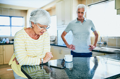 Buy stock photo Cropped shot of a senior woman looking upset while her husband stands in the background