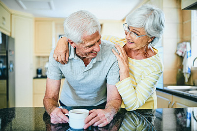 Buy stock photo Shot of a senior man having coffee while standing in the kitchen at home with his wife