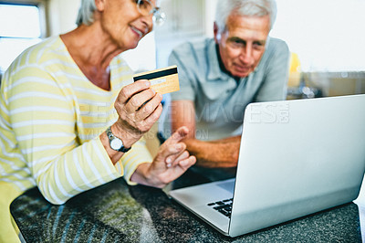 Buy stock photo Shot of a senior woman holding a credit card while using a laptop with her husband at home