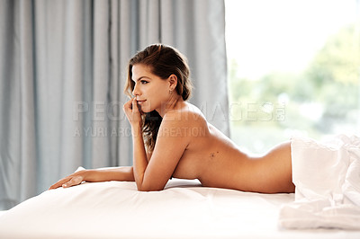 Buy stock photo Cropped shot of a gorgeous young woman looking thoughtful while lying naked on her bed at home