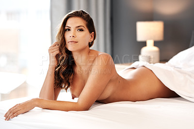 Buy stock photo Cropped portrait of a gorgeous young woman lying naked on her bed at home