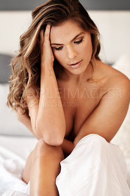 Buy stock photo Cropped shot of a gorgeous young woman looking thoughtful while sitting naked on her bed at home