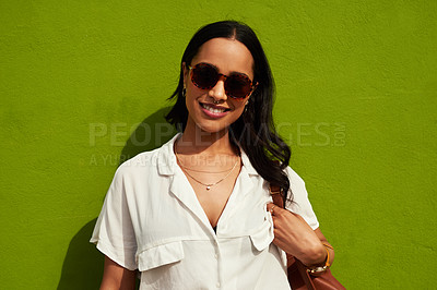 Buy stock photo Cropped portrait of an attractive young woman wearing sunglasses while standing alone against a green background in the city