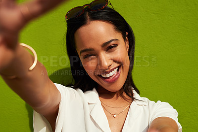 Buy stock photo Cropped portrait of an attractive young woman standing alone and taking a selfie against a green background in the city