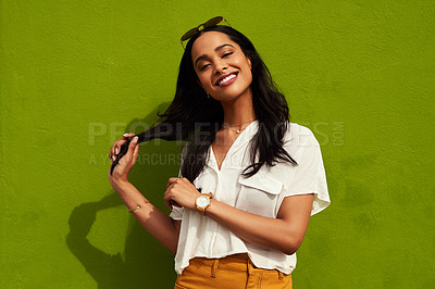 Buy stock photo Cropped portrait of an attractive young woman standing alone against a green background during a day out in the city