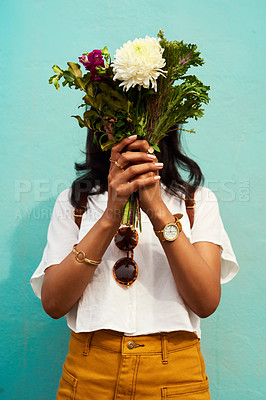 Buy stock photo Cropped shot of an unrecognizable woman standing alone and holding a bouquet of flowers against a blue background