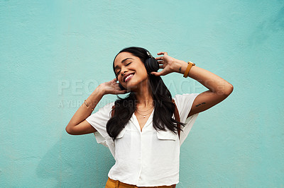 Buy stock photo Cropped shot of an attractive young woman standing alone and dancing while listening to music against a blue background