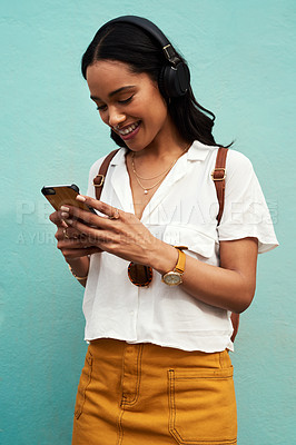 Buy stock photo Cropped shot of an attractive young woman standing alone and listening to music while texting against a blue background