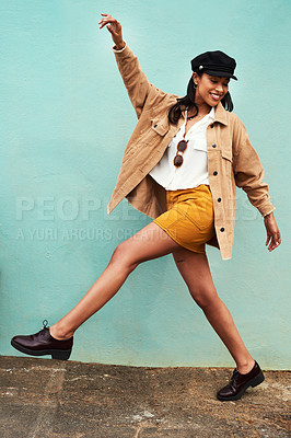 Buy stock photo Full length shot of an attractive young woman feeling playful against a blue background during a day in the city