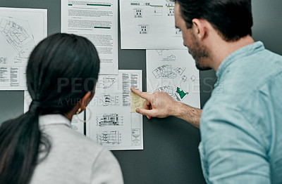 Buy stock photo Rearview shot of two architects working with blueprints on a wall in an office