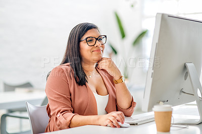Buy stock photo Cropped shot of an attractive young businesswoman sitting alone in her office and looking contemplative while using her computer