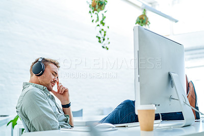 Buy stock photo Cropped shot of a handsome young businessman sitting alone in his office and feeling stressed while wearing headphones
