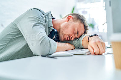 Buy stock photo Cropped shot of a handsome young businessman sitting in his office and sleeping at his desk
