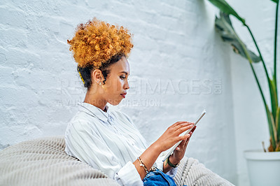 Buy stock photo Cropped shot of an attractive young businesswoman sitting alone in her office and using her tablet