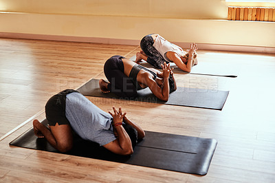 Buy stock photo Shot of a group of young men and women practicing the child's pose during a yoga session