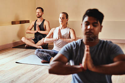 Buy stock photo Shot of a group of young men and women meditating in a yoga class