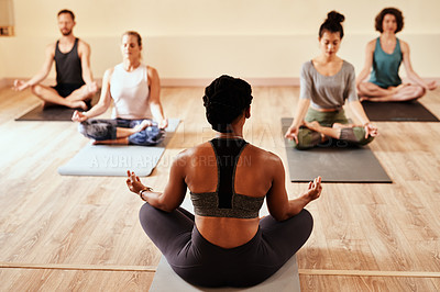 Buy stock photo Shot of a group of young men and women meditating in the lotus position during a yoga session