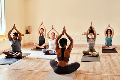 Buy stock photo Shot of a group of young men and women meditating during a yoga session
