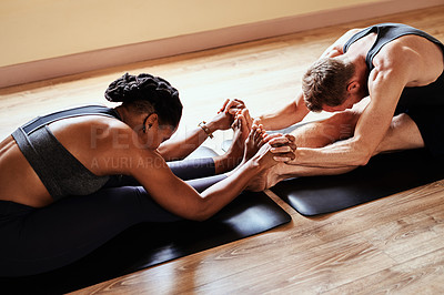 Buy stock photo Shot of a young man and woman holding hands during a yoga session