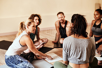Buy stock photo Shot of a group of young men and women chatting during a yoga class