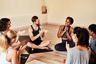 Buy stock photo Shot of a group of young men and women clapping during a yoga class
