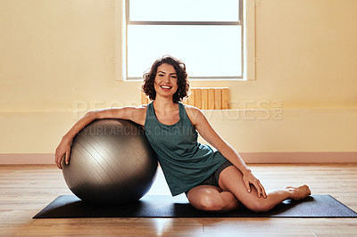 Buy stock photo Shot of a young woman working out with a stability ball during a yoga session