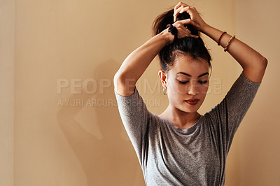 Buy stock photo Shot of a young woman tying up her hair in preparation for a yoga session