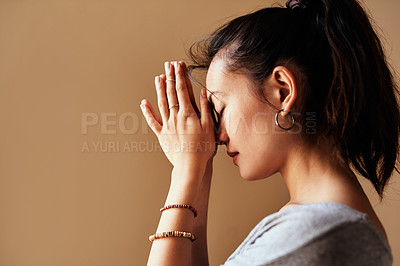 Buy stock photo Shot of a young woman meditating with her hands together against a brown background