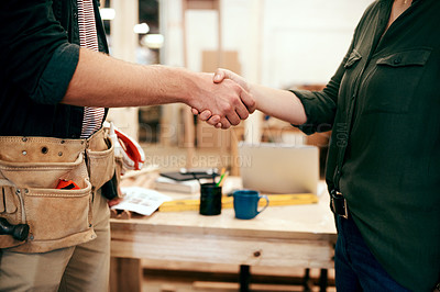 Buy stock photo Cropped shot of two unrecognizable carpenters shaking hands together inside their workshop