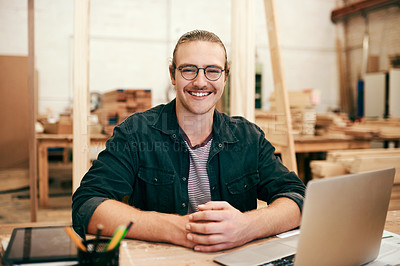 Buy stock photo Portrait of a handsome young carpenter working on a laptop inside his workshop