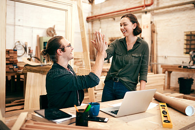 Buy stock photo Cropped shot of two young carpenters joining for a high five while working together inside their workshop