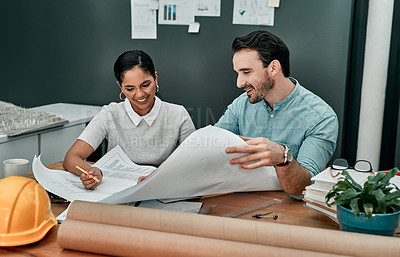 Buy stock photo Shot of two architects working with blueprints in an office
